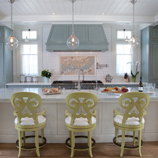 Inspiration for a large beach style u-shaped medium tone wood floor eat-in kitchen remodel in Boston with a drop-in sink, beaded inset cabinets, blue cabinets, marble countertops, multicolored backsplash, ceramic backsplash, stainless steel appliances and an island