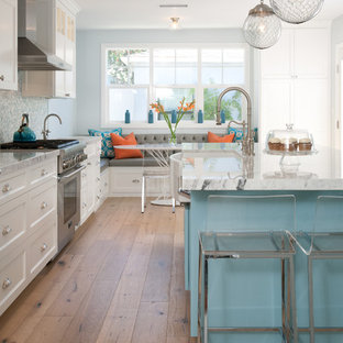 Design ideas for a large beach style l-shaped eat-in kitchen in Denver with a farmhouse sink, shaker cabinets, white cabinets, blue splashback, mosaic tile splashback, stainless steel appliances, medium hardwood floors, an island, beige floor and quartzite benchtops.
