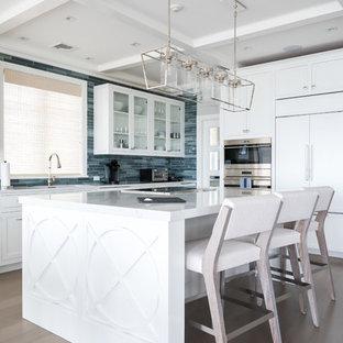 Inspiration för mellanstora maritima linjära vitt kök med öppen planlösning, med en undermonterad diskho, luckor med glaspanel, vita skåp, blått stänkskydd, stänkskydd i glaskakel, rostfria vitvaror, mellanmörkt trägolv, en köksö och brunt golv