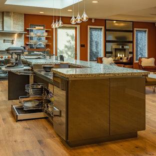 Пример оригинального дизайна: большая угловая кухня-гостиная в современном стиле с врезной раковиной, плоскими фасадами, серыми фасадами, столешницей из переработанного стекла, цветной техникой, островом и паркетным полом среднего тона