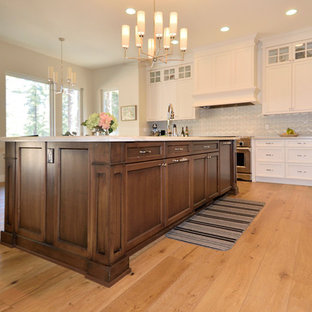 Inspiration for a mid-sized traditional l-shaped eat-in kitchen in Other with an undermount sink, recessed-panel cabinets, turquoise cabinets, granite benchtops, grey splashback, glass tile splashback, stainless steel appliances, medium hardwood floors and with island.