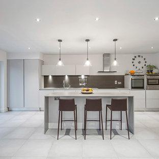 ダブリンの大きいコンテンポラリースタイルのおしゃれなキッチン (一体型シンク、フラットパネル扉のキャビネット、白いキャビネット、大理石カウンター、メタリックのキッチンパネル、メタルタイルのキッチンパネル、パネルと同色の調理設備、セラミックタイルの床) の写真