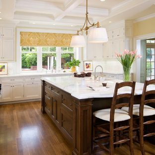 Inspiration for a large timeless u-shaped medium tone wood floor and brown floor enclosed kitchen remodel in San Francisco with beaded inset cabinets, white cabinets, marble countertops, white backsplash, paneled appliances, a farmhouse sink, an island and marble backsplash