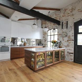 ロンドンの大きいシャビーシック調のおしゃれなキッチン (アンダーカウンターシンク、フラットパネル扉のキャビネット、中間色木目調キャビネット、大理石カウンター、メタリックのキッチンパネル、ガラス板のキッチンパネル、シルバーの調理設備の、無垢フローリング) の写真