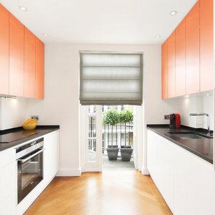 Zweizeilige, Mittelgroße Moderne Küche ohne Insel mit flächenbündigen Schrankfronten, Küchenrückwand in Weiß, Küchengeräten aus Edelstahl, hellem Holzboden, Unterbauwaschbecken, orangefarbenen Schränken und Granit-Arbeitsplatte in London