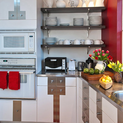 Eat-in kitchen - large eclectic limestone floor and beige floor eat-in kitchen idea in San Francisco with white appliances, stainless steel countertops, white cabinets, a drop-in sink, flat-panel cabinets, gray backsplash, metal backsplash and a peninsula