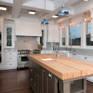 Example of a classic kitchen design in Portland with shaker cabinets, stainless steel appliances, wood countertops, a farmhouse sink, white cabinets and blue backsplash