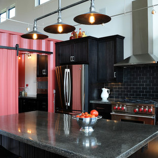 Photo of a mid-sized industrial single-wall open plan kitchen in Other with black cabinets, black splashback, stainless steel appliances, medium hardwood floors, with island, recessed-panel cabinets, concrete benchtops and ceramic splashback.