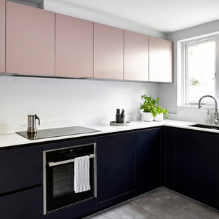 Photo of a contemporary l-shaped kitchen in London with a submerged sink, flat-panel cabinets, black cabinets, stainless steel appliances, grey floors and white worktops.