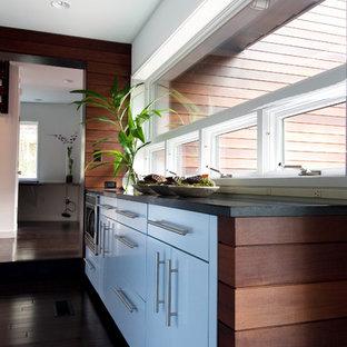 Idee per una cucina moderna chiusa e di medie dimensioni con ante lisce, ante bianche, elettrodomestici in acciaio inossidabile, top in saponaria e isola
