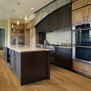 Large modern open concept kitchen appliance - Large minimalist single-wall bamboo floor open concept kitchen photo in Orlando with an undermount sink, shaker cabinets, dark wood cabinets, granite countertops, stainless steel appliances and an island