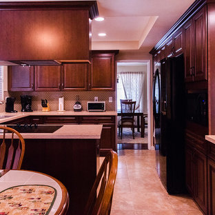 Photo of a large traditional u-shaped eat-in kitchen in Orange County with an undermount sink, raised-panel cabinets, dark wood cabinets, quartz benchtops, metallic splashback, glass tile splashback, black appliances, ceramic floors, with island and beige floor.