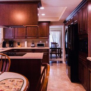 На фото: большая п-образная кухня в классическом стиле с обеденным столом, врезной раковиной, фасадами с выступающей филенкой, темными деревянными фасадами, столешницей из кварцевого агломерата, фартуком цвета металлик, фартуком из стеклянной плитки, черной техникой, полом из керамической плитки, островом и бежевым полом