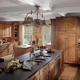 Inredning av ett amerikanskt mellanstort kök, med en trippel diskho, luckor med upphöjd panel, skåp i mellenmörkt trä, bänkskiva i koppar, rostfria vitvaror, mellanmörkt trägolv och en köksö
