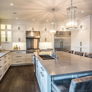 Example of a trendy l-shaped kitchen design in Toronto with an undermount sink, shaker cabinets, white cabinets, quartz countertops, gray backsplash, stone tile backsplash, stainless steel appliances and gray countertops
