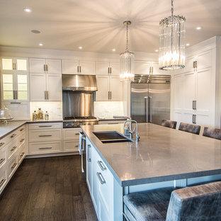 Diseño de cocina en L, actual, con fregadero bajoencimera, armarios estilo shaker, puertas de armario blancas, encimera de cuarzo compacto, salpicadero verde, salpicadero de azulejos de piedra, electrodomésticos de acero inoxidable y encimeras grises