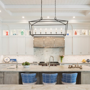 Beach style kitchen inspiration - Inspiration for a beach style u-shaped kitchen remodel in Other with stainless steel appliances, an island, recessed-panel cabinets, yellow cabinets and white backsplash