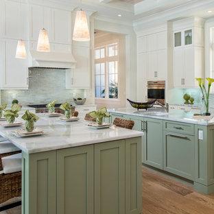 Idéer för att renovera ett vintage kök, med en undermonterad diskho, skåp i shakerstil, gröna skåp, grått stänkskydd, stänkskydd i glaskakel, rostfria vitvaror, ljust trägolv och flera köksöar