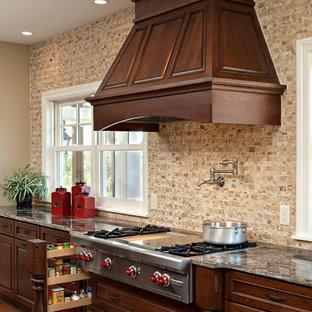 Новый формат декора квартиры: кухня в классическом стиле с техникой из нержавеющей стали, бежевым фартуком, темными деревянными фасадами и фартуком из травертина