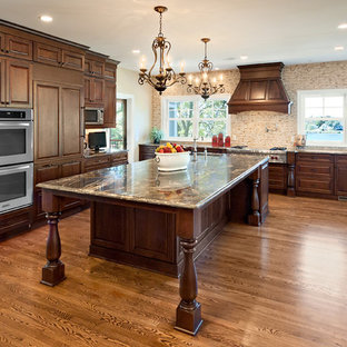 Kitchen - traditional kitchen idea in Minneapolis with raised-panel cabinets, dark wood cabinets, beige backsplash and paneled appliances