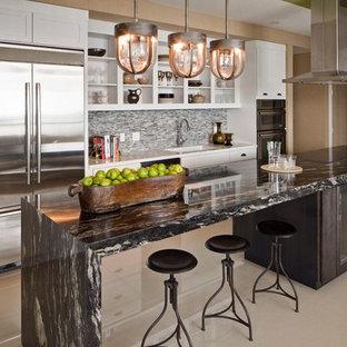 Idéer för eklektiska linjära kök och matrum, med en undermonterad diskho, luckor med glaspanel, vita skåp, granitbänkskiva, stänkskydd med metallisk yta, stänkskydd i mosaik och rostfria vitvaror