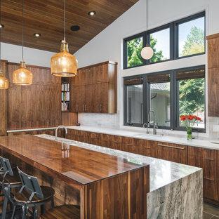 Midcentury modern kitchen ideas - Midcentury modern l-shaped gray floor kitchen photo in Portland with an undermount sink, flat-panel cabinets, dark wood cabinets, beige backsplash, paneled appliances, an island and white countertops