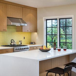 Moderne Wohnküche in L-Form mit flächenbündigen Schrankfronten, hellbraunen Holzschränken, Quarzwerkstein-Arbeitsplatte, Küchenrückwand in Gelb, Rückwand aus Keramikfliesen, Küchengeräten aus Edelstahl, braunem Holzboden und Kücheninsel in Portland