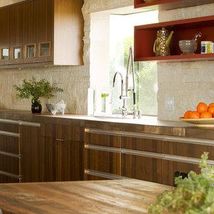 Ejemplo de cocina vintage con armarios con paneles lisos, puertas de armario de madera en tonos medios, encimera de madera, salpicadero beige y salpicadero de piedra caliza
