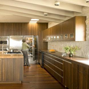 Midcentury kitchen in Orange County with stainless steel appliances, flat-panel cabinets, dark wood cabinets, wood benchtops, beige splashback and stone tile splashback.