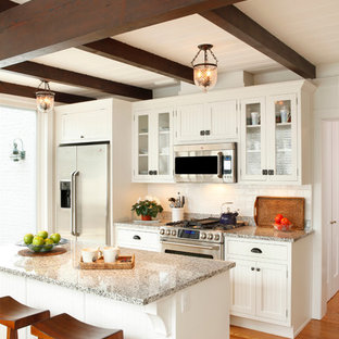 Small traditional eat-in kitchen remodeling - Inspiration for a small timeless single-wall medium tone wood floor and brown floor eat-in kitchen remodel in Other with glass-front cabinets, white cabinets, white backsplash, ceramic backsplash, stainless steel appliances, an island and granite countertops
