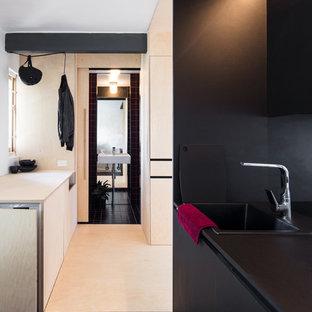 メルボルンの小さいアジアンスタイルのおしゃれなI型キッチン (シングルシンク、黒いキャビネット、ラミネートカウンター、ガラス板のキッチンパネル、黒い調理設備、セラミックタイルの床、アイランドなし、黒い床、黒いキッチンカウンター) の写真