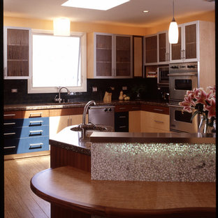 Design ideas for a mid-sized contemporary l-shaped open plan kitchen in San Diego with a single-bowl sink, glass-front cabinets, light wood cabinets, recycled glass benchtops, black splashback, stainless steel appliances, bamboo floors and with island.