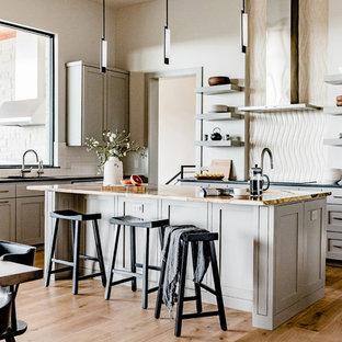 Moderne Küche mit Schrankfronten im Shaker-Stil, Granit-Arbeitsplatte, Küchenrückwand in Beige, Kalk-Rückwand, hellem Holzboden und Kücheninsel in Austin