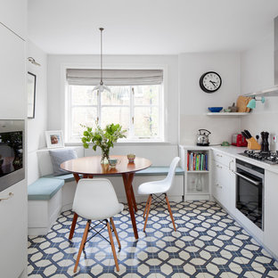 This is an example of a small contemporary galley kitchen/diner in London with flat-panel cabinets, white cabinets, ceramic flooring and no island.