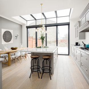Design ideas for a medium sized classic single-wall kitchen/diner in London with recessed-panel cabinets, grey cabinets, light hardwood flooring, an island, beige floors, white worktops, marble worktops, grey splashback and marble splashback.