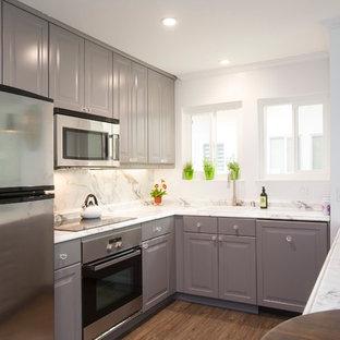 オレンジカウンティの小さいトランジショナルスタイルのおしゃれなキッチン (グレーのキャビネット、ラミネートカウンター、アンダーカウンターシンク、白いキッチンパネル、石スラブのキッチンパネル、シルバーの調理設備、カーペット敷き、レイズドパネル扉のキャビネット、茶色い床) の写真