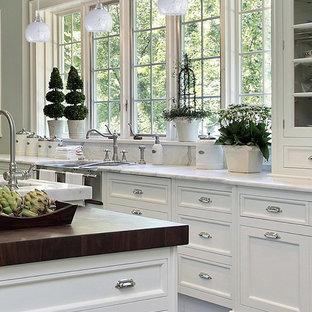 ニューヨークの中サイズのアジアンスタイルのおしゃれなキッチン (ドロップインシンク、フラットパネル扉のキャビネット、ヴィンテージ仕上げキャビネット、珪岩カウンター、グレーのキッチンパネル、ガラスタイルのキッチンパネル) の写真
