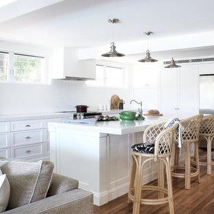 This is an example of a beach style l-shaped open plan kitchen in Sydney with a farmhouse sink, shaker cabinets, white cabinets, granite benchtops, white splashback, ceramic splashback, stainless steel appliances, with island, white benchtop, medium hardwood floors and brown floor.