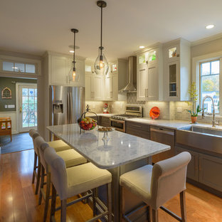 Mid-sized transitional eat-in kitchen designs - Eat-in kitchen - mid-sized transitional l-shaped light wood floor eat-in kitchen idea in Boston with a farmhouse sink, shaker cabinets, gray cabinets, quartz countertops, ceramic backsplash, an island and gray backsplash