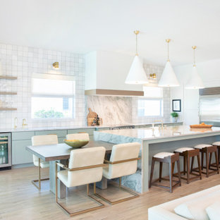 This is an example of a large beach style l-shaped eat-in kitchen in Miami with a single-bowl sink, shaker cabinets, green cabinets, quartzite benchtops, multi-coloured splashback, stone slab splashback, stainless steel appliances, porcelain floors, with island, grey floor and multi-coloured benchtop.