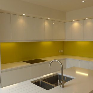 Inspiration for a medium sized contemporary l-shaped open plan kitchen in Other with a submerged sink, flat-panel cabinets, white cabinets, quartz worktops, yellow splashback, glass sheet splashback, stainless steel appliances, porcelain flooring, an island, beige floors and yellow worktops.