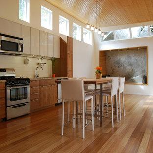 На фото: с невысоким бюджетом маленькие линейные кухни в стиле модернизм с фасадами цвета дерева среднего тона, белым фартуком, фартуком из плитки кабанчик, техникой из нержавеющей стали, фасадами в стиле шейкер, столешницей из гранита, полом из бамбука и островом
