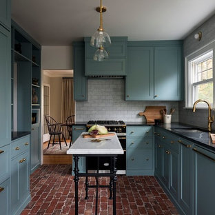 This is an example of a medium sized victorian l-shaped enclosed kitchen in Portland with a submerged sink, shaker cabinets, blue cabinets, soapstone worktops, grey splashback, marble splashback, integrated appliances, brick flooring, an island, red floors and black worktops.
