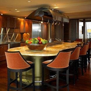 Стильный дизайн: большая линейная кухня в современном стиле с обеденным столом, раковиной в стиле кантри, плоскими фасадами, темными деревянными фасадами, столешницей из оникса, фартуком цвета металлик, фартуком из металлической плитки, техникой из нержавеющей стали, темным паркетным полом и островом - последний тренд