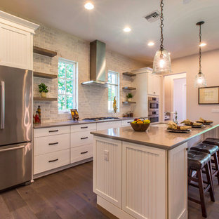 Large farmhouse kitchen ideas - Inspiration for a large farmhouse single-wall dark wood floor kitchen remodel in Orlando with white cabinets, granite countertops, stainless steel appliances, an undermount sink, flat-panel cabinets, gray backsplash and an island
