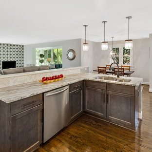 Photo of a mid-sized midcentury u-shaped eat-in kitchen in Wilmington with an undermount sink, recessed-panel cabinets, distressed cabinets, granite benchtops, white splashback, marble splashback, stainless steel appliances, dark hardwood floors, a peninsula, brown floor and multi-coloured benchtop.