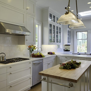 Photo of a mid-sized traditional l-shaped eat-in kitchen in San Francisco with stainless steel appliances, subway tile splashback, white cabinets, solid surface benchtops, white splashback, with island, a drop-in sink, shaker cabinets and cork floors.