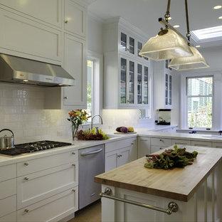 Неиссякаемый источник вдохновения для домашнего уюта: угловая кухня среднего размера в классическом стиле с техникой из нержавеющей стали, фартуком из плитки кабанчик, белыми фасадами, столешницей из акрилового камня, белым фартуком, островом, накладной раковиной, обеденным столом, фасадами в стиле шейкер и пробковым полом
