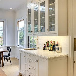 サンフランシスコの広いトラディショナルスタイルのおしゃれなキッチン (サブウェイタイルのキッチンパネル、アンダーカウンターシンク、ガラス扉のキャビネット、白いキャビネット、白いキッチンパネル、大理石カウンター、コルクフローリング、シルバーの調理設備) の写真
