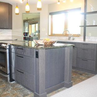 大きいコンテンポラリースタイルのおしゃれなキッチン (アンダーカウンターシンク、フラットパネル扉のキャビネット、グレーのキャビネット、ライムストーンカウンター、ベージュキッチンパネル、石タイルのキッチンパネル、シルバーの調理設備の、スレートの床、ベージュの床、緑のキッチンカウンター) の写真
